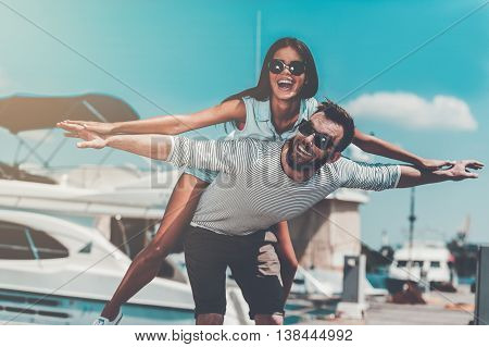 Carefree fun. Playful young man carrying his beautiful girlfriend on shoulders while standing on quay
