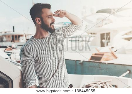 Nice view! Confident young man looking forward and smiling while standing on the board of yacht