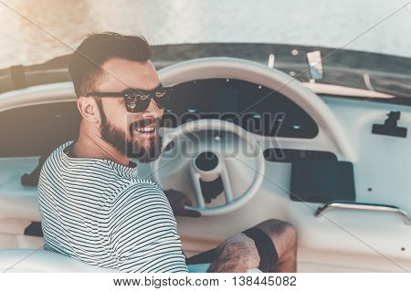Cheerful yacht owner. Smiling young man holding hand on steering wheel while driving yacht