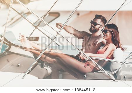 Just look over there! Happy young couple looking forward with smiles while sitting on the board of yacht