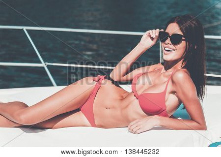 Enjoying high life. Beautiful young woman in red bikini adjusting eyewear and smiling at camera while lying on the deck of yacht