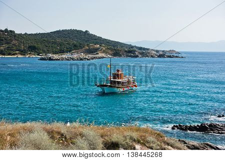 Ship is sailing to small Sarti harbor, mount Athos in background, Sithonia, Greece