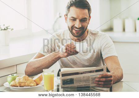Starting day with good news. Handsome young man reading newspaper and smiling while drinking coffee and having breakfast in the kitchen