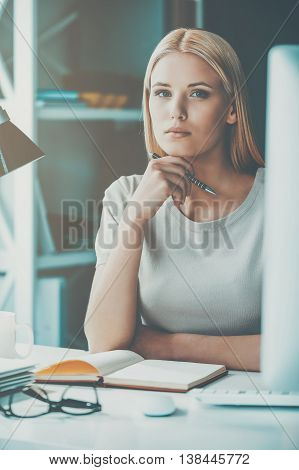 Confident businesswoman. Beautiful young woman holding hand on chin and looking at camera while sitting at her working place in office