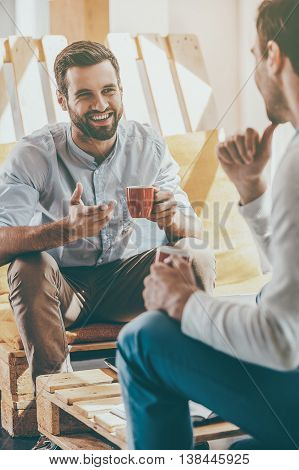 Discussing business. Two young men holding cups of coffee and discuss something while sitting in the rest area of the office