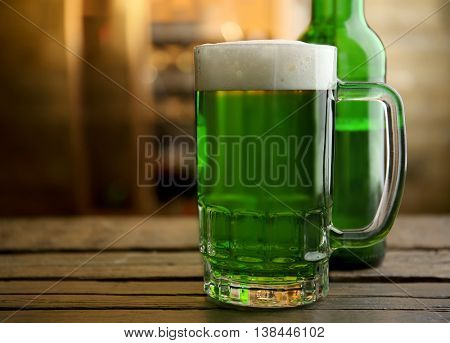 Glass of green beer and bottle on blurred bar background