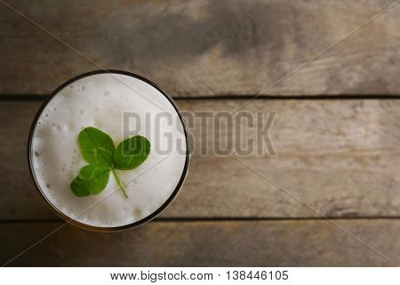 Glass of beer with clover leaf on wooden background