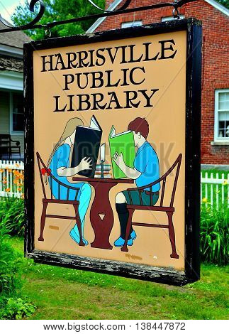 Harrisville New Hampshire - July 11 2013: Charming sign showing two youngsters reading books in front of the Harrisville Public Library