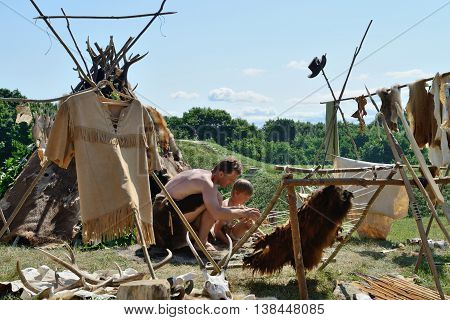 KERNAVE, LITHUANIA - JULY 7: Unidentified people at 14th International Festival of Experimental Archaeology on July 7, 2013. Its a most popular folklore event on July in Lithuania