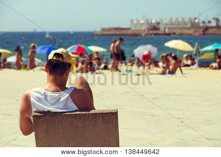 BARCELONA, SPAIN - JULY 10: People at Nova Icaria Beach on July 10, 2016 in Barcelona, Spain, with the Port Olimpic in the background. This busy beach is mainly frequented by the locals