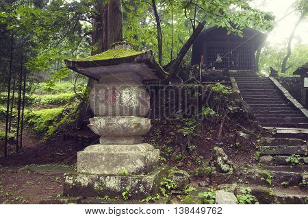 ancient stone lantern structure in Japanese temple yard in Nikko Tochigi prefecture