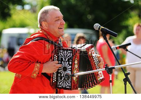 Orel Russia - July 08 2016: Russian Valentine Day - Petr and Fevronia. Senior man in red outfit playing garmoshka Russian accordion closeup