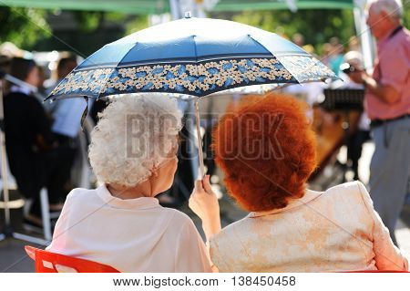 Orel Russia - July 08 2016: Russian Valentine Day - Petr and Fevronia. Two senior women with dyed hair under umbrella closeup
