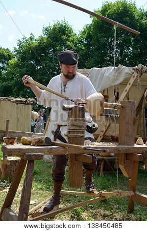 KERNAVE, LITHUANIA - JULY 7: Unidentified people carve wood in the 14th International Festival of Experimental Archaeology on July 7, 2013. Its a most popular folklore event on July in Lithuania
