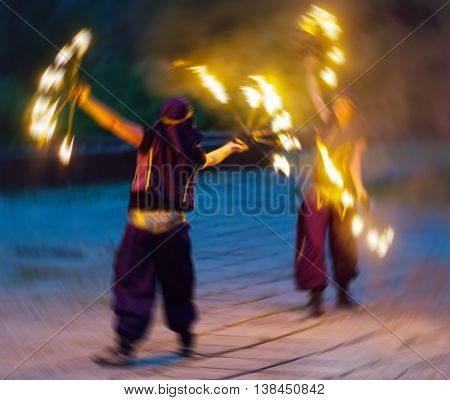 Horizontal vivid two female fakir playing with fire motion abstraction background backdrop