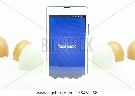 BUNG KAN THAILAND - MARCH 08 2016: smart phone display facebook app on easter theme background