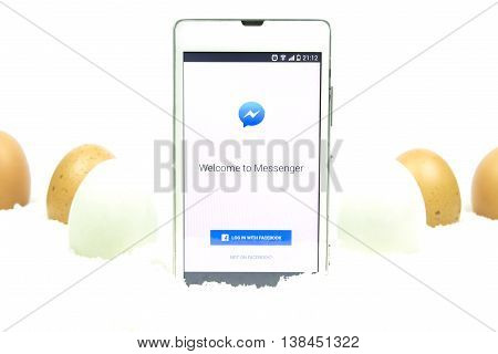 BUNG KAN THAILAND - MARCH 08 2016: smart phone display facebook messenger app on easter theme background