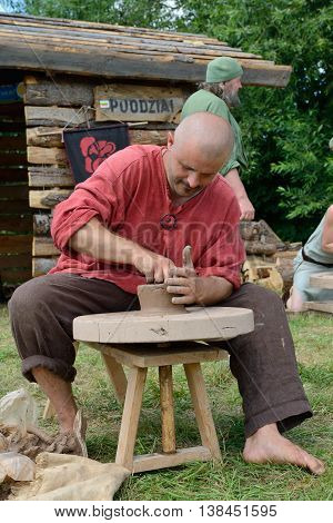 KERNAVE, LITHUANIA - JULY 7: Unidentified people make a jug at 14th International Festival of Experimental Archaeology on July 7, 2013. Its a most popular folklore event on July in Lithuania