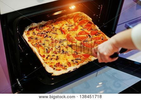 Woman Cut With A Knife Homemade Pizza In Electric Oven In The Kitchen