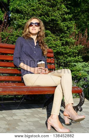Stylish Woman In Sunglasses With Disposable Coffee Cup Sitting On Bench