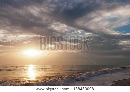 The landscape with sunset over the sea and the dramatic cloudy sky