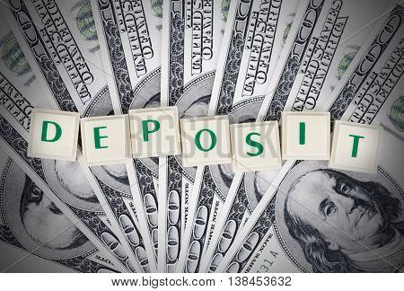 Deposit sing on stack of 100 dollars