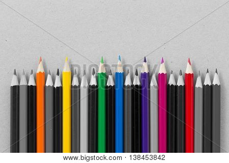 Several sharpened wooden colored pencils among the gray ones on gray background. Concept of creation of team of professionals