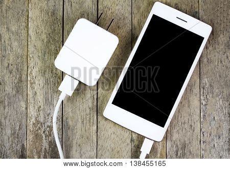 smart phone and adapter charger on wood background