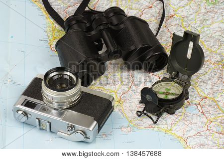 Porro binoculars, military compass and old rangefinder analog camera lying on the map.