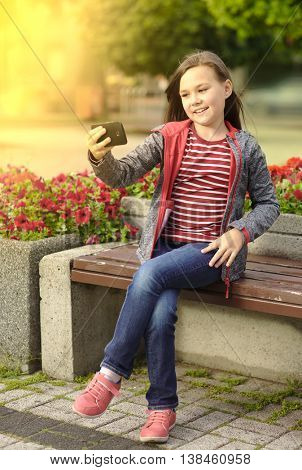Girl is making photo using a phone, outdoor shoot