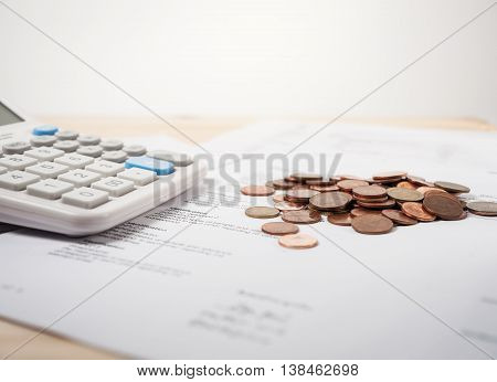 Bill of medication with calculator and coins on white background