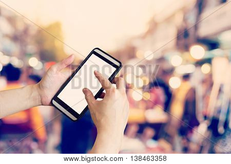 Hand Using Smartphone And Blurred Crowd Of People Walking Through A City Street. Vintage Toned Photo