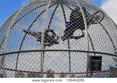 PORVOO, FINLAND - JULY 2, 2016: Cage Riders Show on the annual Riverside Truck Meeting 2016. The two Finnish stunt riders Pasi Heikkila and Sasja Laajoki ride motorcycles inside a steel mesh sphere ball.