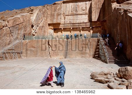 PERSEPOLIS, IRAN - OCT 22, 2014: Unidentified girls play next to the historical tomb of persian king Artaxerxes III on October 22, 2014. UNESCO declared citadel of Persepolis a World Heritage Site in 1979