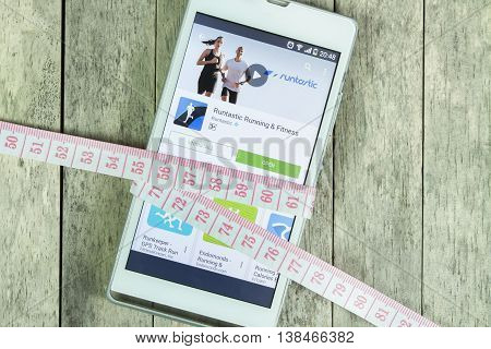 BUNG KAN THAILAND - FEBRUARY 21 2016: smart phone display runtastic app and measure tape on office desk