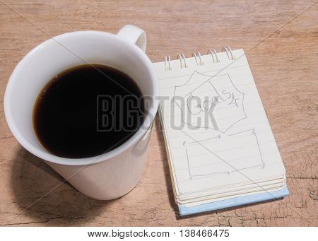 White Cup Of Coffee And Litter Notebook With Word