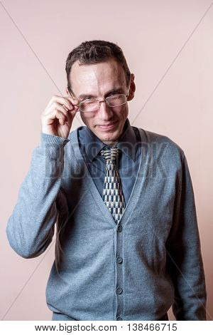 man with smile wearing eyeglasses in a gray cardigan on a colored background