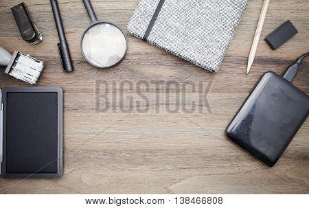 Workstation concept top view : Stapler,pen,magnifier,book,pencil,harddisk,keyboard on wooden background.In film tone