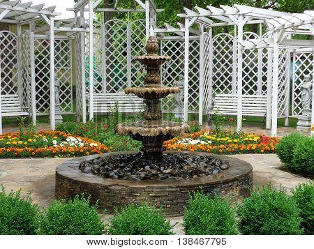 PRIMORSK, UKRAINE - ИЮНЬ JUNE 12, 2016: Fountain in front of a white wooden gazebo in the park. Photo taken on a summer morning