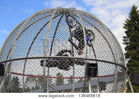 PORVOO FINLAND - JULY 2 2016: Cage Riders Show on the annual Riverside Truck Meeting 2016. The two Finnish stunt riders Sasja Laajoki and Pasi Heikkila ride loops on motorcycles inside a mesh sphere ball both horizontally and vertically.