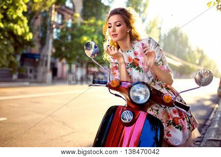 Girl On Scooter Paints Her Lips With Lipstick Looking In The Rearview Mirror