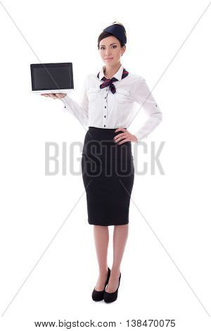 Full Length Portrait Of Young Stewardess Showing Laptop With Blank Screen Isolated On White