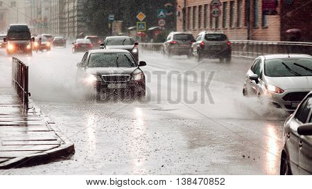 Moving car sprays a puddle when heavy rain drops