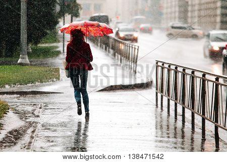 Woman runs with umbrella when heavy rain drops.