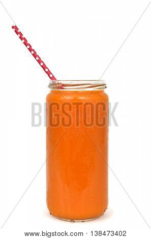 an orange detox smoothie served in a glass jar with a red drinking straw patterned with white dots, isolated on a white background