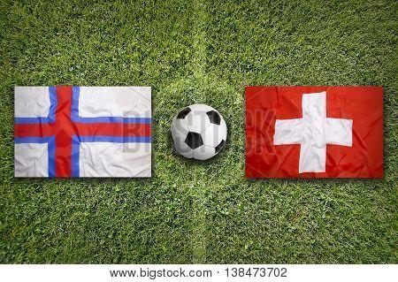 Faeroe Islands Vs. Switzerland Flags On Soccer Field