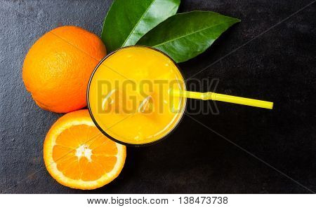 Glass of freshly squeezed orange juice, fresh oranges and leaves on black background. Top view