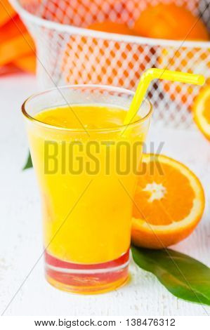 Glass of freshly squeezed orange juice, fresh oranges ib basket and leaves on white background. Closeup