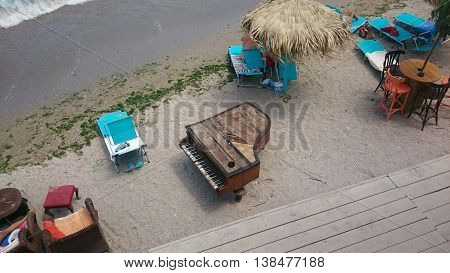 Piano on sea coast. Vintage piano on beach.