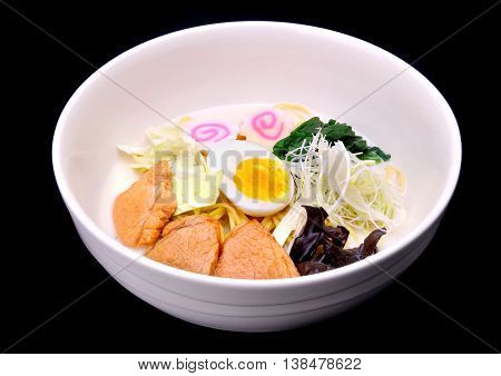 Japanese noodles in white pork bones soup with pork big piece photo in studio lighting.